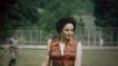 1963: Italian American women walks park plaid sleeveless shirt. Stock Footage