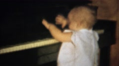1963: Cute blonde baby learning piano plays keys smiles laughs. Stock Footage