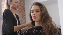 Stylist curling hair for young woman. Slow motion. Close up Stock Footage