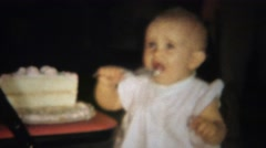 1963: Blonde baby girl eating half birthday cake with spoon. Stock Footage