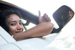 Young woman shows thumb up from open window of the white car - stock photo