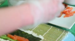 Sushi master puts a red fish on nori Stock Footage