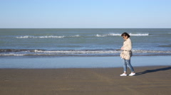 Depressed young woman near the sea in a windy day. Beautiful young brunette woma Stock Footage