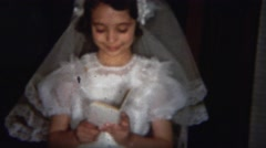 1964: Sweet young humble girl reading bible practicing holy communion. - stock footage
