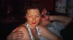 1964: Drunk man puts arm around unsure pretty women. - stock footage