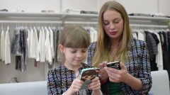 Mam and Daughter with Smartphones and Mobile phone shating in clothes store Stock Footage