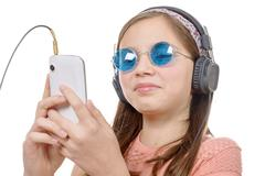 preteen girl listening to music with his smartphone, on white - stock photo