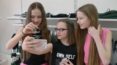 Three girls having fun and doing selfie mobile phone shopping in a clothing stor Stock Footage
