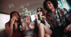 Stock Video Footage of Hipster friends having fun with bubbles inside a vintage van