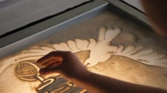 Girl draws painting with sand on the glass Stock Footage