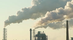 Long shot of fumes rising from factory chimneys - stock footage