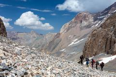 Group of Hikers Walking on Deserted Rocky Terrain - stock photo