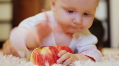 Little girl with an apple, trying to bite him Stock Footage