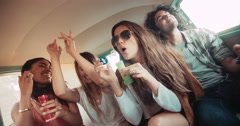 Hipster friends having bubbles party inside a vintage van Stock Footage