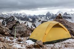 Yellow tent on mountain landscape - stock photo