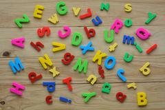 Top lay of scattered English letters on a wooden background - stock photo