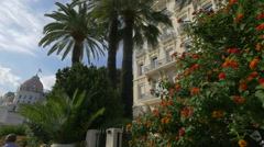 Palm trees and flowers in front of West End Hotel in Nice Stock Footage