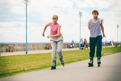 Two people race together riding rollerblades. - stock photo
