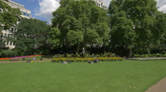 Sitting on grass in Victoria Embankment Gardens in London Stock Footage