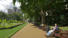 Sitting on benches in Victoria Embankment Gardens in London Stock Footage