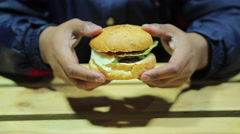 Stock Video Footage of Hungry man considering burger. Unhealthy lunch. Fast food. Cholesterol. Obesity