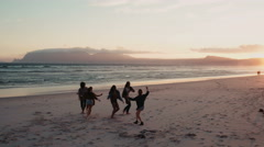 Silhouette of teen friends dancing on the beach at sunset - stock footage