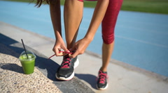 Fitness woman runner tying running shoes with green smoothie on athletic track Stock Footage