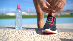 Sports woman runner getting ready for run tying running shoes with water bottle Stock Footage