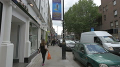 People walking by the famous stores of Long Acre in London - stock footage