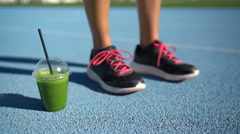 Fitness shoes and green smoothie juice cup on running track Stock Footage