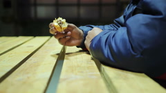 Charity event. Hungry man eating and enjoying tasty but fatty burger. Fast food - stock footage