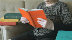 Old grandmother reading the book on the couch Stock Footage