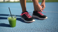 Female runner tying shoes for track running with breakfast green smoothie cup - stock footage