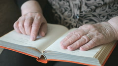 Old hands of the old woman holding a book Stock Footage
