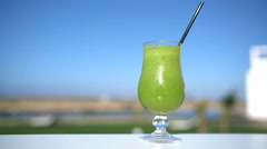 Green vegetable smoothie juice glass on restaurant table closeup at outdoor cafe Stock Footage