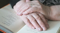 Old grandmother flipping through the book - stock footage
