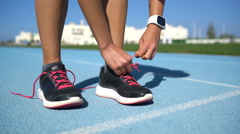 Runner woman tying running shoes getting ready for race on run track Stock Footage