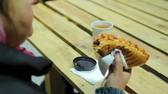 Junk food. Plump woman eating fatty hot dog and drinking hot tea. Overweight Stock Footage