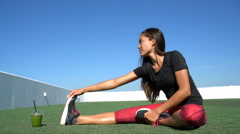 Seated one-legged toe touch woman stretching on outdoor fitness gym grass Stock Footage