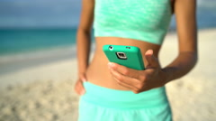 Fitness woman on beach using smartphone app on 4g or texting sms Stock Footage
