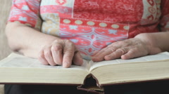Old woman reading the pages of the thick book Stock Footage
