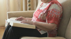 Old woman reading the book on the couch Stock Footage