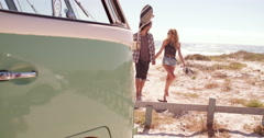 Hipster couple walking together barefoot towards van from beach Stock Footage