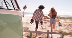 Hipster couple walking barefoot onto beach from road trip van Stock Footage