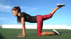 Donkey kick leg workout fitness woman working out glutes on grass floor outside Stock Footage