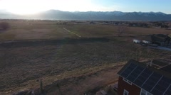 Aerial shot of a house with solar panels and mountain at sunset Stock Footage