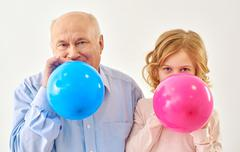 Granddaughter and grandfather inflating balloons in studio Stock Photos