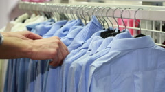 Hand clothes shop. blue sweaters and shirts Stock Footage