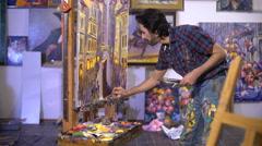 senior man painting on a canvas - stock footage