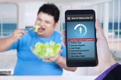 Healthy resolutions app with man eats salad - stock photo